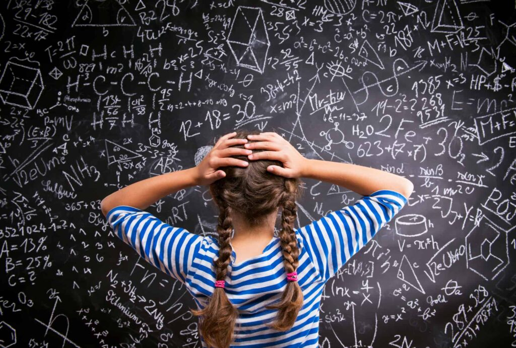 Girl with hands on head looking at a chalkboard